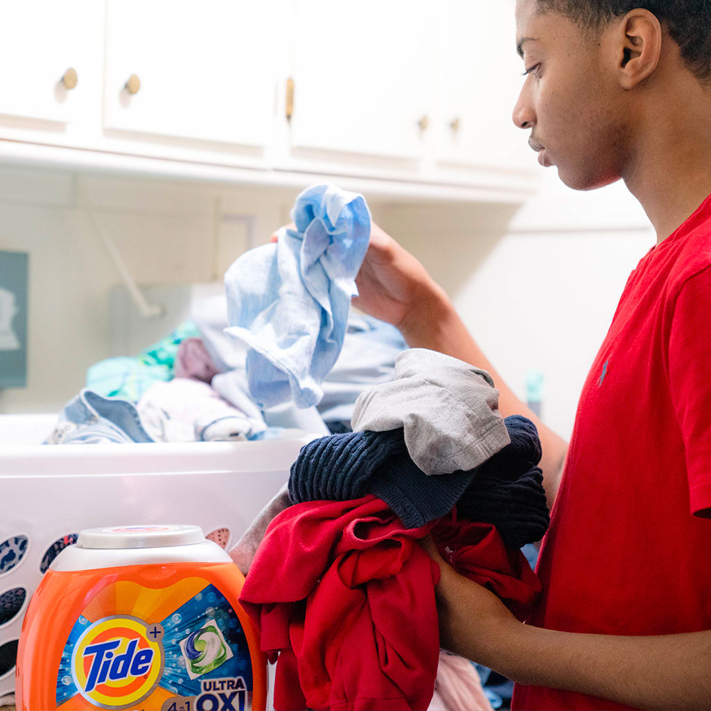 teen doing laundry with Tide PODS