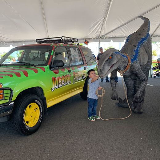 boy touching dinosaur next to Jurassic Park SUV