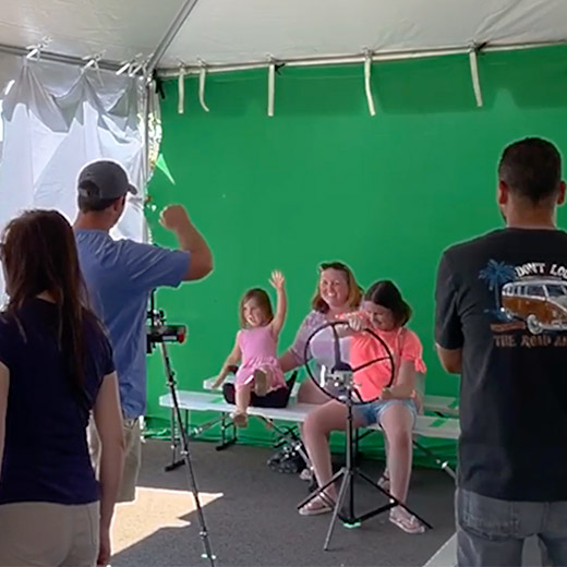 family participating in green screen Famous Cars simulation