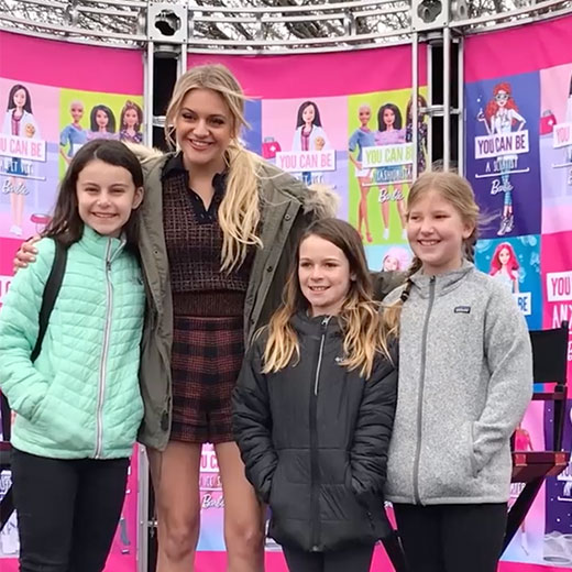 girls posing for photo with a female influencer at Barbie event