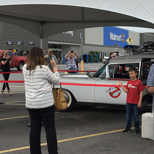 mom and son taking a photo with Ghostbusters car at Famous Cars event