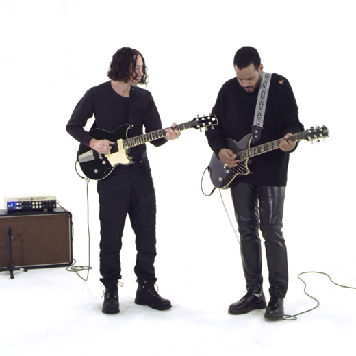 two male musicians playing Yamaha guitars